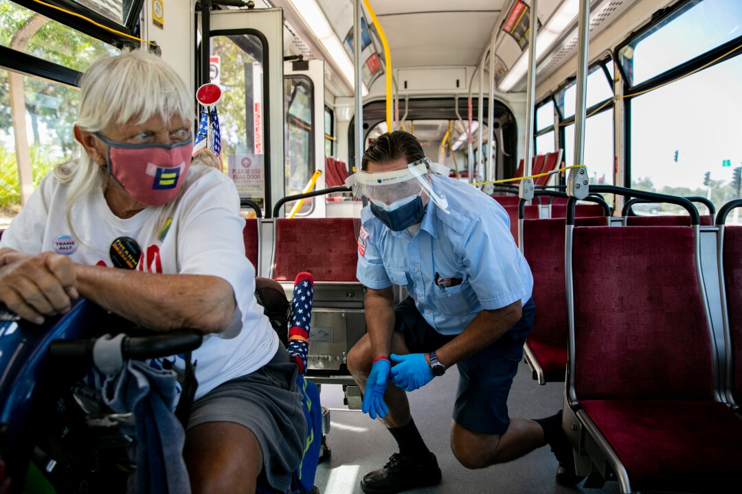 Christopher Castor, 56, helps a passenger in a wheelchair get secured into the number 7 bus.