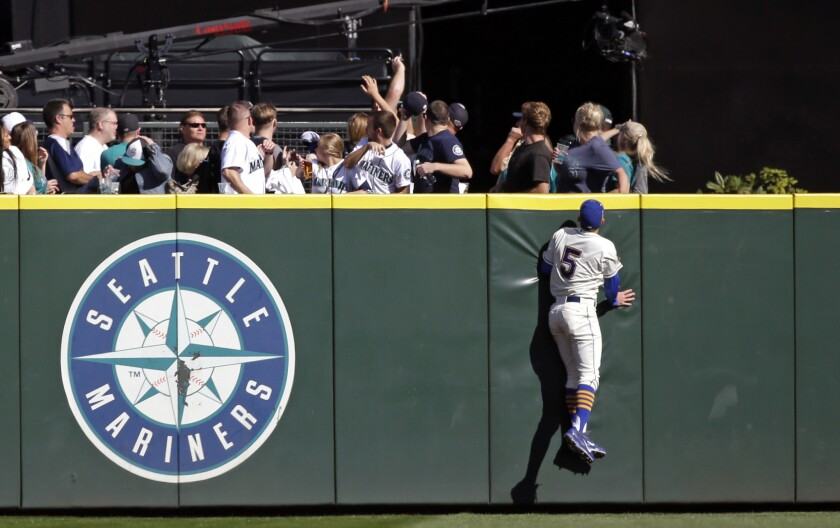 Seattle Mariners center fielder Brad Miller watches fans reach for the home run ball of Oakland Athletics' Mark Canha in the third inning of a game on Oct. 4.