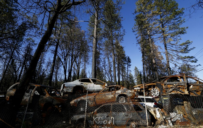 Charred cars from the Camp fire are stacked in a lot in Paradise
