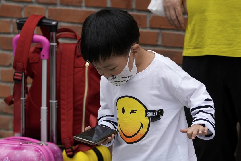 A child wearing a face mask plays game on a smartphone next to his relative in Beijing Sept. 12, 2021. Chinese regulators have set up a platform that allows the public to report on gaming companies they believe are violating restrictions on online game times for children. (AP Photo/Andy Wong)
