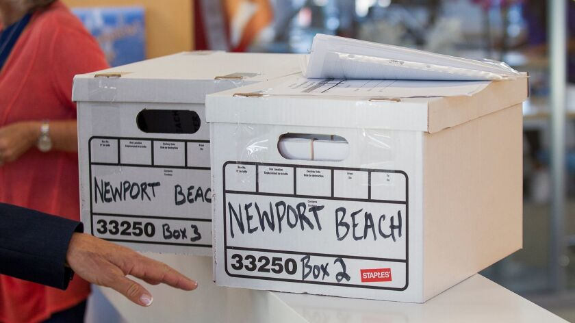 Two boxes filled with 10,684 petitions wait to be counted by the Newport Beach city clerk on on Frid