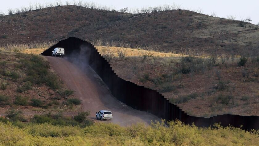 FILE - In this Oct. 2, 2012 file photo, U.S. Border Patrol agents patrol the border fence in Naco, A