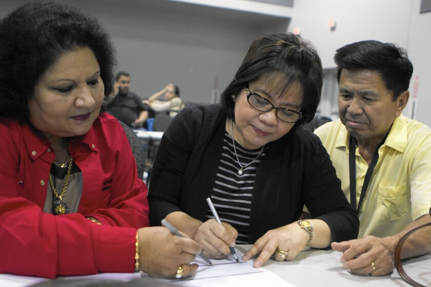 Mortgage consultant Anna Datta, left, helps Grace and Armando Ong sign up for a 15-year home loan at a Neighborhood Assistance Corp. of America event at the Ontario Convention Center.