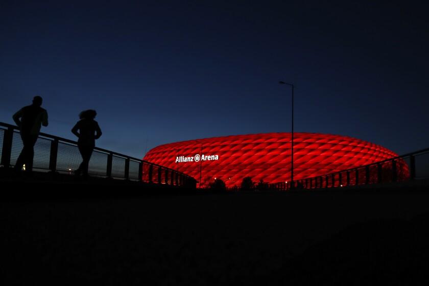 ARCHIVO -- En esta foto del 16 de marzo de 2020, una pareja trota al atardecer en el estadio Allianz Arena en Múnich. (AP Foto/Matthias Schrader)