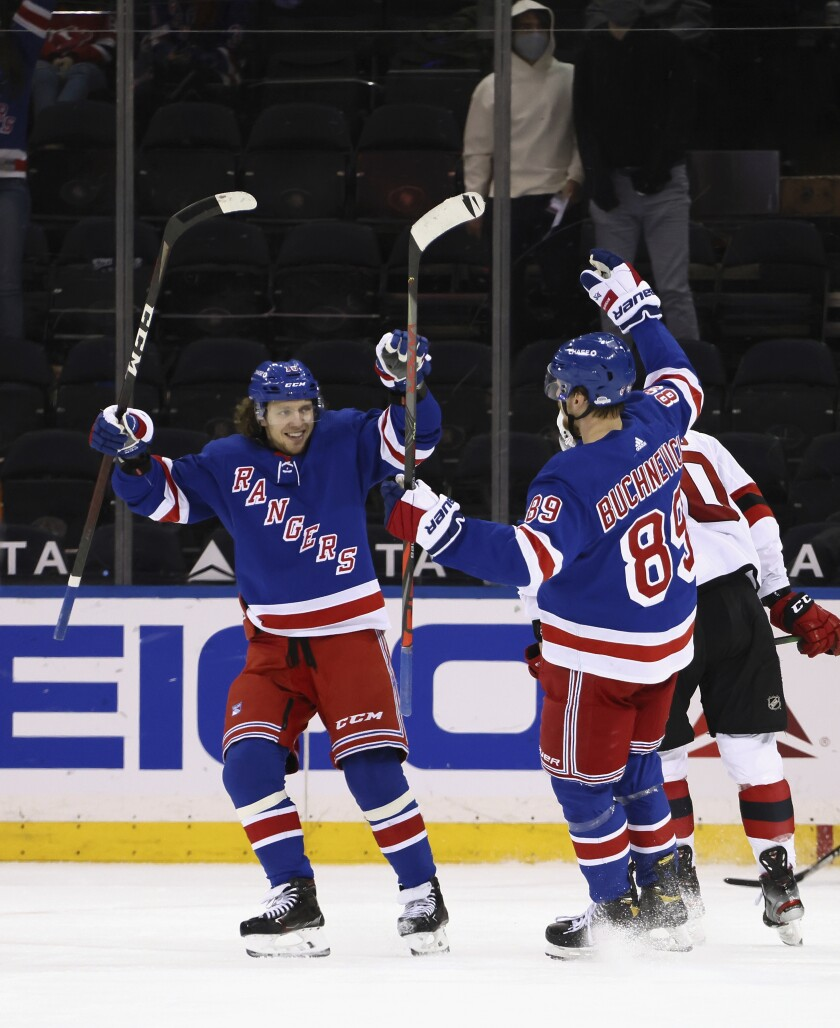 New York Rangers' Pavel Buchnevich (89) and Artemi Panarin celebrate after Buchnevich scored his third goal against the New Jersey Devils in the third period of an NHL hockey game, Saturday, April 17, 2021, in New York. (Bruce Bennett/Pool Photo via AP)