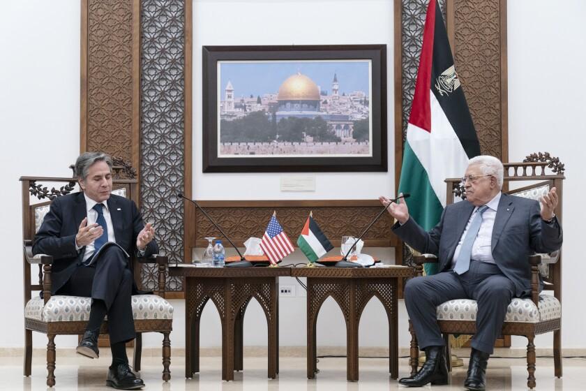 Antony Blinken, left, and Mahmoud Abbas, both seated, gesture as they speak