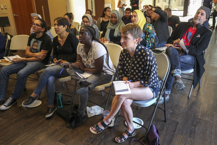 A group of mostly young adults watch the Democratic presidential debate during a watch party, put on by Youth Will, at the Jacobs Center For Neighborhood Innovation on June 26.