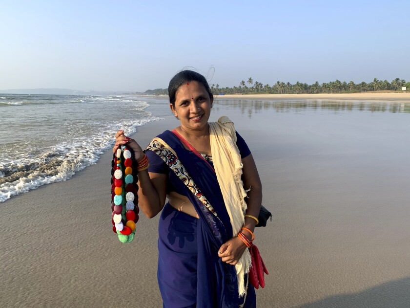 """Seema Rajgarh, 37, hawks jewelry made of beads and stones on nearly deserted Utorda beach in South Goa, India,, Dec.16, 2020. On good days during the holiday season, the mother of three girls, the youngest not yet two years old, said she used to make 2,000 rupees ( $27). Now, times are bleak. """"Some days, I make barely 200 rupees ($2.7), not enough to even buy milk and food for my children,"""" she said. """"This virus has devastated our lives,"""" Rajgarh said. Goans are mourning the loss of their livelihoods and possibly their way of life to the pandemic and travel restrictions. (AP Photo/Vineeta Deepak)"""