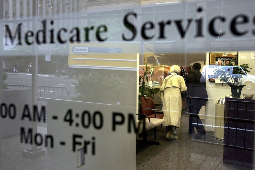 Two people walk inside a Medicare Services office in New York City in 2006.