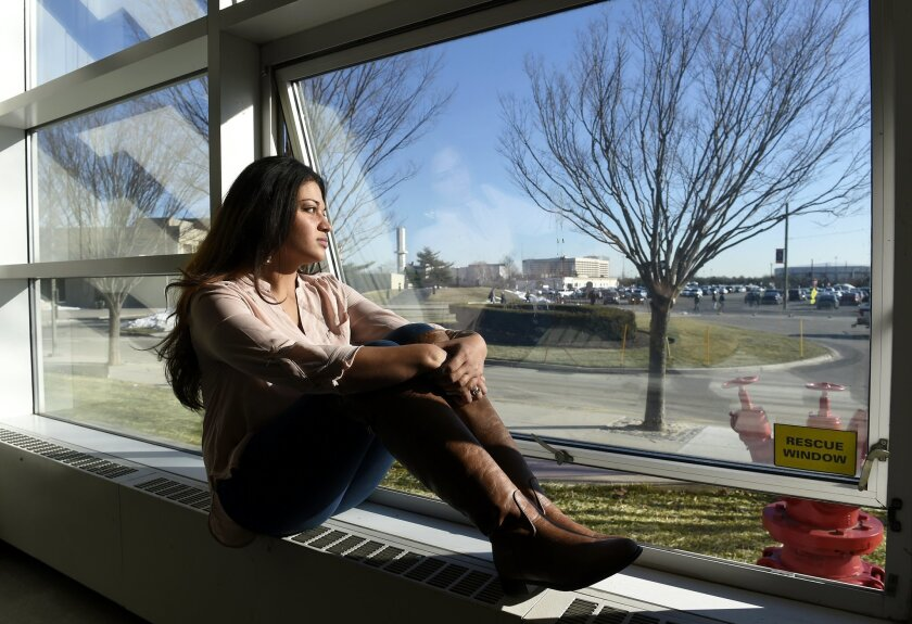 In this Feb. 2, 2016 photo, Naila Amin, 26, looks out from a classroom window at Nassau Community College where she is a student in Garden City, N.Y. Amin, who was forced into marriage at the age of 15 to a 28-year-old cousin in Pakistan who beat and mistreated her, aspires to become a social worke