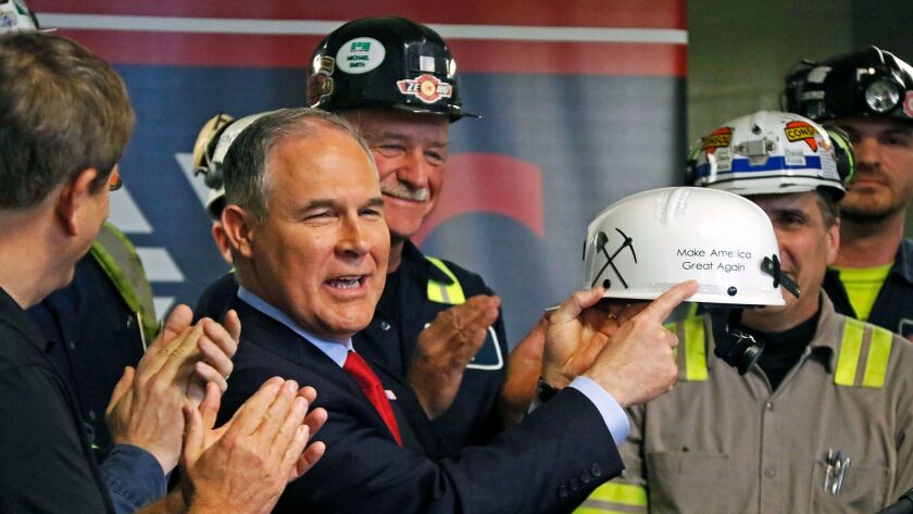 """Environmental Protection Agency Administrator Scott Pruitt holds up a """"Make America Great Again"""" hardhat he was given during a visit to a coal mine in Sycamore, Pa. on April 13."""