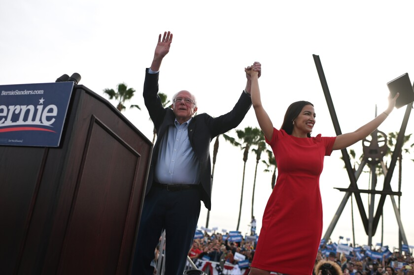 Sen. Bernie Sanders and Rep. Alexandria Ocasio-Cortez take the stage at a campaign rally in Venice on Dec. 21.