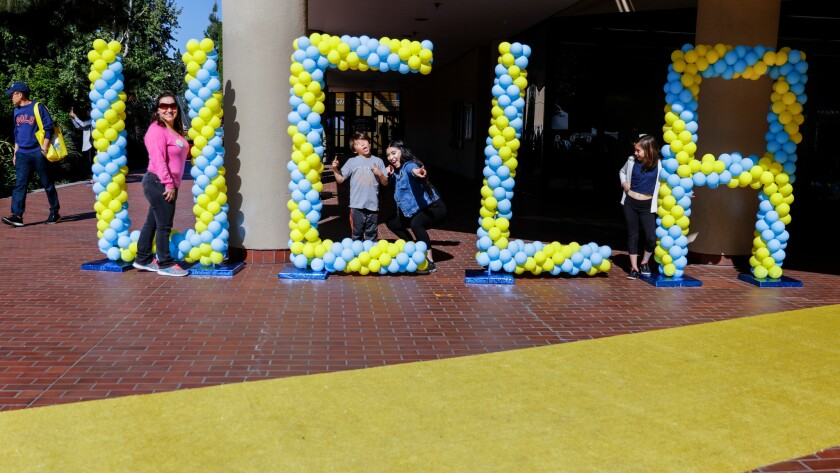 Janet Mejia, left, from Sun Valley and her kids Emmanuel, Jennifer and Samantha, from left, pose for pictures with balloons spelling UCLA, during the annual Bruins Day.