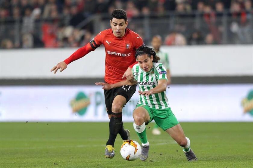 El centrocampista mexicano del Betis Diego Lainez (d) disputa un balón con el centrocampista francés del Rennes Benjamin Andre durante el partido entre ambos equipos correspondiente a los dieciseisavos de final de la Liga Europa de la UEFA, este jueves en Rennes (Francia). EFE