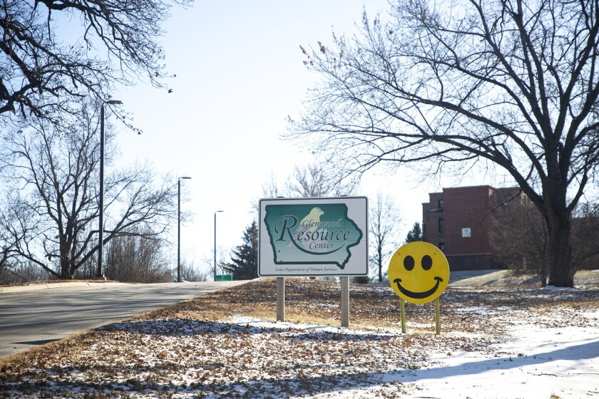 This photo taken Dec. 19, 2019, shows a sign with a smiling face greets drivers as they enter the Glenwood Resource Center campus in Glenwood, Iowa. Two doctors and other former employees of an Iowa care center for people with intellectual disabilities have filed a federal civil rights lawsuit Monday, Feb. 10, 2020, against a state agency and several officials alleging a conspiracy to silence complaints about sexual arousal research they claim exploited fragile and dependent residents. (Kelsey Kremer/The Des Moines Register via AP)