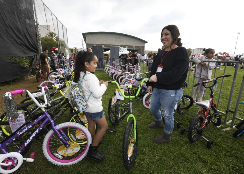 Volunteer Samantha Aguilar, right, helps Mia Ruiz, 7, pick out a bike that she won at the Toys for Joy event held at Lincoln High School Saturday. The annual event is put on by the Rock Church.
