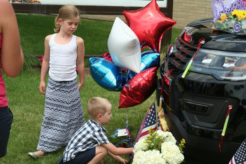Lily and Keegan Goff, the children of Berrien County Sheriff SWAT team Deputy Justin Goff, place flowers Tuesday, July 12, 2016, at a memorial for slain court officers Joe Zangaro and Ron Kienzle in St. Joseph, Mich.. Deputy Goff was one of the first responders when the fatal shootings at the Berrien County Courthouse occurred Monday. (John Matuszak/The Herald-Palladium via AP)