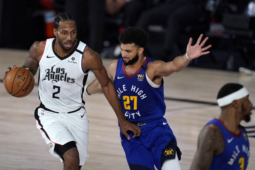 Clippers forward Kawhi Leonard drives against Nuggets guard Jamal Murray during Game 5 on Sept. 11, 2020.