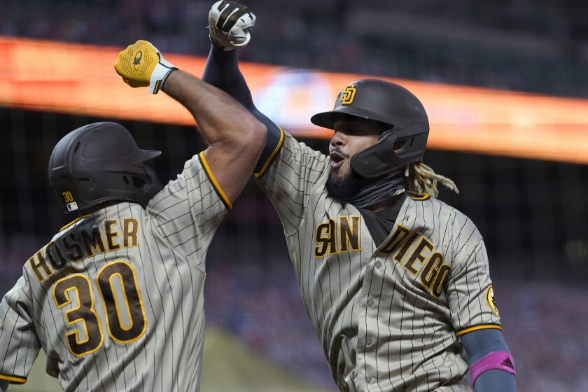 San Diego Padres' Fernando Tatis Jr., right, is congratulated by Eric Hosmer after hitting a solo home run against the San Francisco Giants during the fourth inning of a baseball game in San Francisco, Saturday, Sept. 26, 2020. (AP Photo/Eric Risberg)