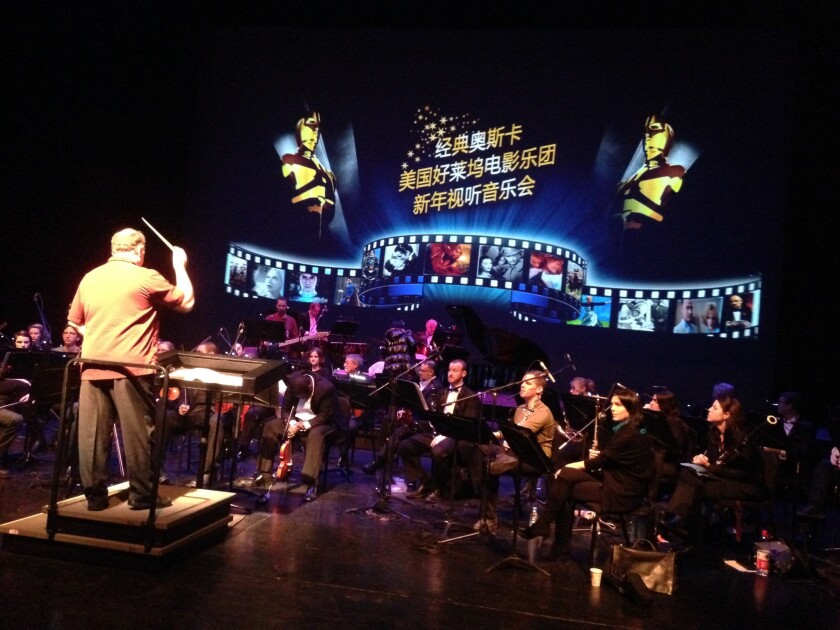 "Members of the American Hollywood Film Orchestra rehearse at the National Center for the Performing Arts in Beijing. The screen behind them reads, ""Classic Oscar: The American Hollywood Film Orchestra New Year's Audio-Visual Concert."""