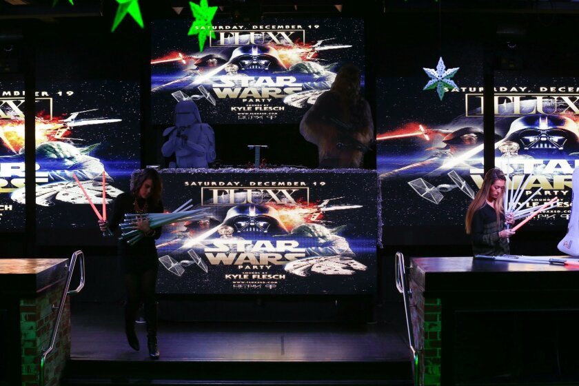SAN DIEGO, CA-DECEMBER 15, 2015: Savanna Rakofsky (left, cq) and Morgan Jensen from the nightclub Fluxx in the Gaslamp Quarter placed and arranged Star Wars light sabers next to a large Darth Vader. In the background are large LED screens displaying Star Wars images. The night club is gearing up for Saturday's celebration of the Star Wars movies where guest are encouraged to arrive dressed as characters from the movie Star Wars. (Nelvin C. Cepeda / San Diego Union-Tribune)