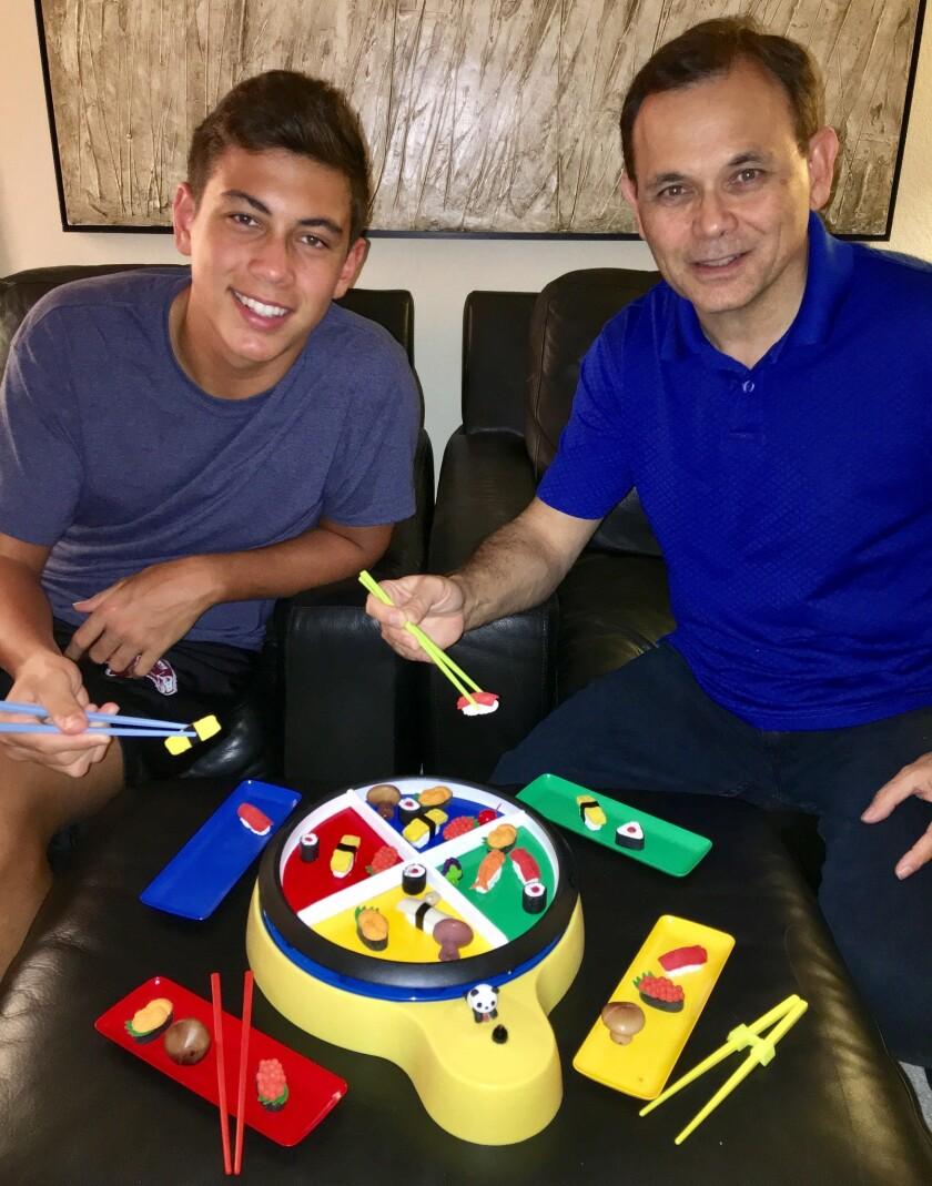 "Chuck Labitan and his son, Christian, with Labitan's game, ""GoChopstix"""