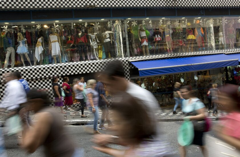 FILE - In this Dec. 1, 2015 file photo taken with a slow shutter speed, people walk through a shopping district in Sao Paulo, Brazil. On Thursday, Feb. 18, 2016, Brazil's central bank reported the economy contracted just over four percent in 2015. Brazil is experiencing its deepest recession since