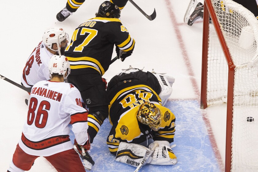 Boston Bruins goaltender Tuukka Rask (40) watches the puck cross the line on what would be ruled no goal due to goalie interference as Carolina Hurricanes' Teuvo Teravainen (86), Hurricanes' Jordan Martinook (48) and Bruins' Torey Krug (47) look on during third-period NHL hockey first-round Stanley Cup playoff action in Toronto, Thursday, Aug. 13, 2020. (Chris Young/The Canadian Press via AP)