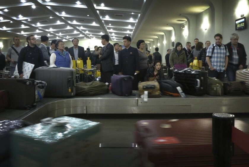 FILE - In this Oct. 21, 2014 file photo, passengers wait for their luggage upon arrival at the Sunan International Airport in Pyongyang, North Korea, before closing its door for foreign visitors to visit the country in fear of the Ebola virus. Tightening the screws even further on travel to their a
