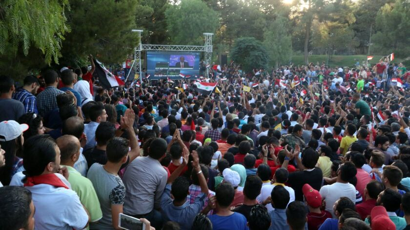 Via a government-erected screen in a park in Damascus, soccer fans watch their national team play in a World Cup 2018 qualifying match in Iran.