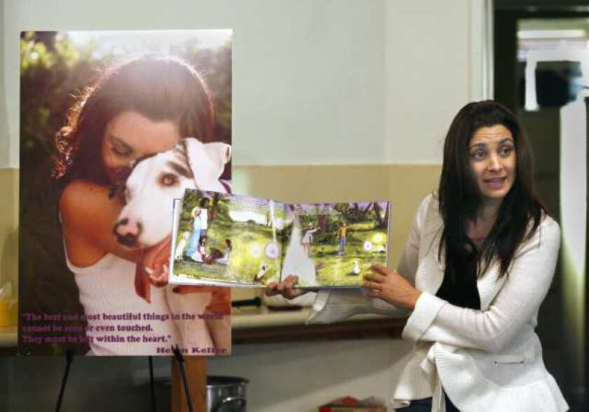 Maryam Faresh, of Studio City, reads What About Daisy? to clients at BCR in Burbank, on Monday, November 29, 2010. The book is about her dog Daisy who is blind and deaf, and shortly after reading the book, the clients at BCR were able to meet Daisy in person.