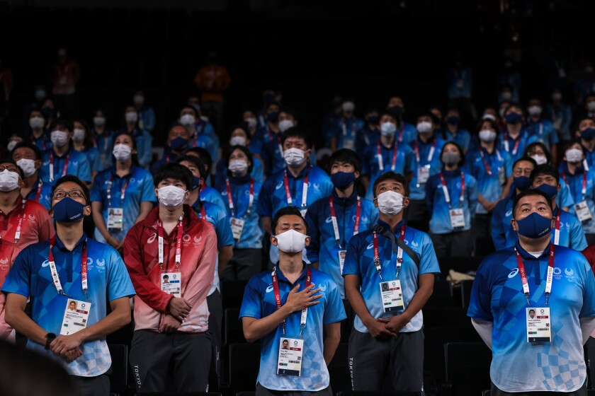 Masked Tokyo Olympics volunteers and staff stand spaced out.