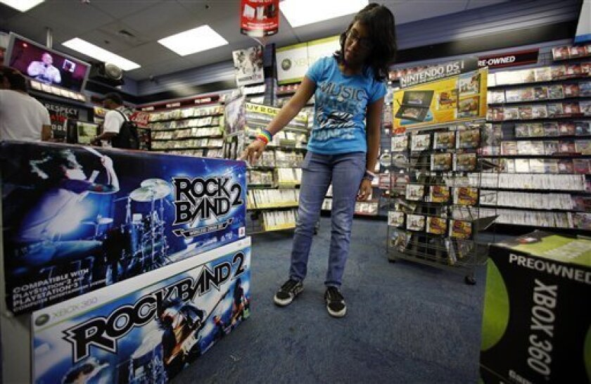 FILE - In this Aug. 28, 2009 file photo, video gamer Paulette Rivera, 13, checks a guitar for her video console at the Game Stop store in Los Angeles, Calif. Starting Sunday, June 13, 2010, video game makers will go big to try to convince you that fancy 3-D screens, gesture-recognition cameras and ultra-sensitive motion controllers topped with brightly glowing spheres are what you need to have a good time. (AP Photo/Damian Dovarganes, file)