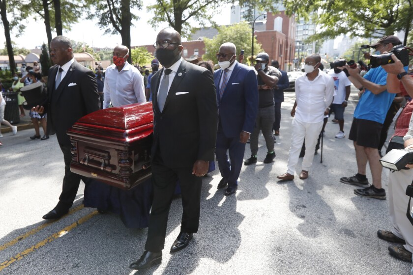 Mourners march with the casket of the Rev. C.T. Vivian in Atlanta