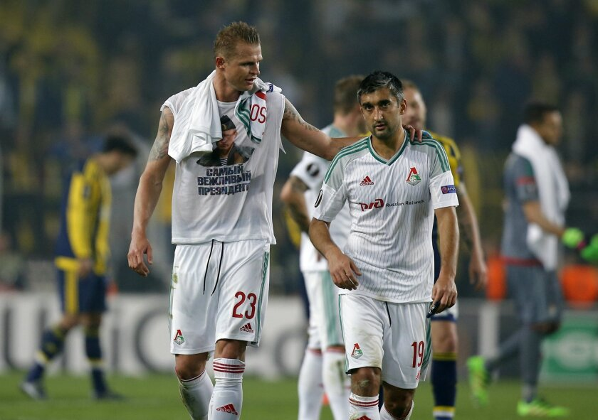 Locomotiv Moscow's Dmitri Tarasov featuring an inner shirt with a picture of Russian President Vladimir Putin walks with his teammate Aleksandr Samedov, following a Europa League first leg round of 32, soccer match against Fenerbahce in Istanbul, Tuesday, Feb. 16, 2016. Fenerbahce won the match 2-0