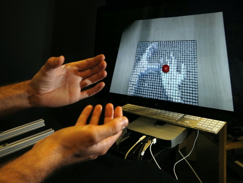 In a Nov. 26, 2013, photo, Massachusetts Institute of Technology graduate student Sean Follmer demonstrates inFORM technology on campus in Cambridge, Mass. Follmer, a researcher with MIT's Tangible Media Group, moves his hands in front of a depth-sensing camera which sends signals to a motorized pin screen in another location where a 3D image pops up to manipulate the red ball. (AP Photo/Elise Amendola)