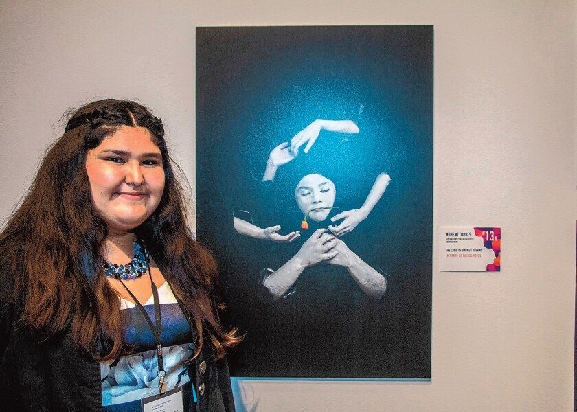 Nohemi Torres, 13, with her 'Land of Broken Dreams' at Museum of Photographic Arts in Balboa Park, San Diego. She has been studying art for six years at the after-school Generations Center for Youth Advancement in City Heights.