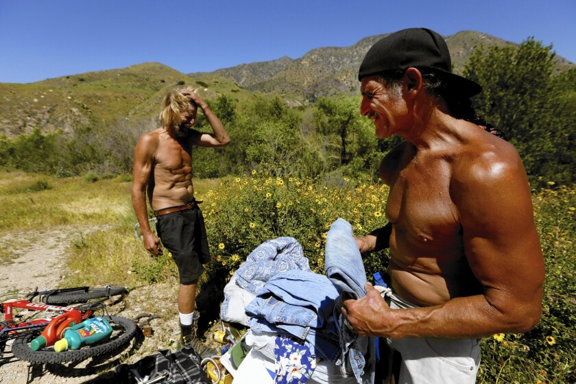 Dave Curry, right, visits his friend Russell Badgwell in Tujunga Wash, the place he used to call home. Curry received a Section 8 voucher from a San Fernando Valley housing agency and now lives in an apartment.