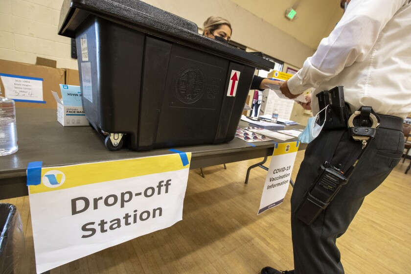 A police officer drops off ballots for the gubernatorial recall election at the Boyle Heights Senior Center on Sept. 14.