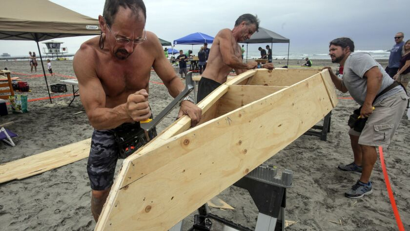 From left, Brian Fest, John Wilson and Antonio DuPont of the Sin Ancla team build a boat during the