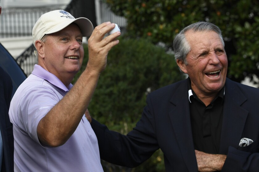 Sen. Lindsey Graham, R-S.C., left, holds up a golf ball as he shares a laugh with golfer Gary Player after they returned to the White House in Washington, Saturday, Sept. 28, 2019, after spending the day playing golf with President Donald Trump. (AP Photo/Susan Walsh)