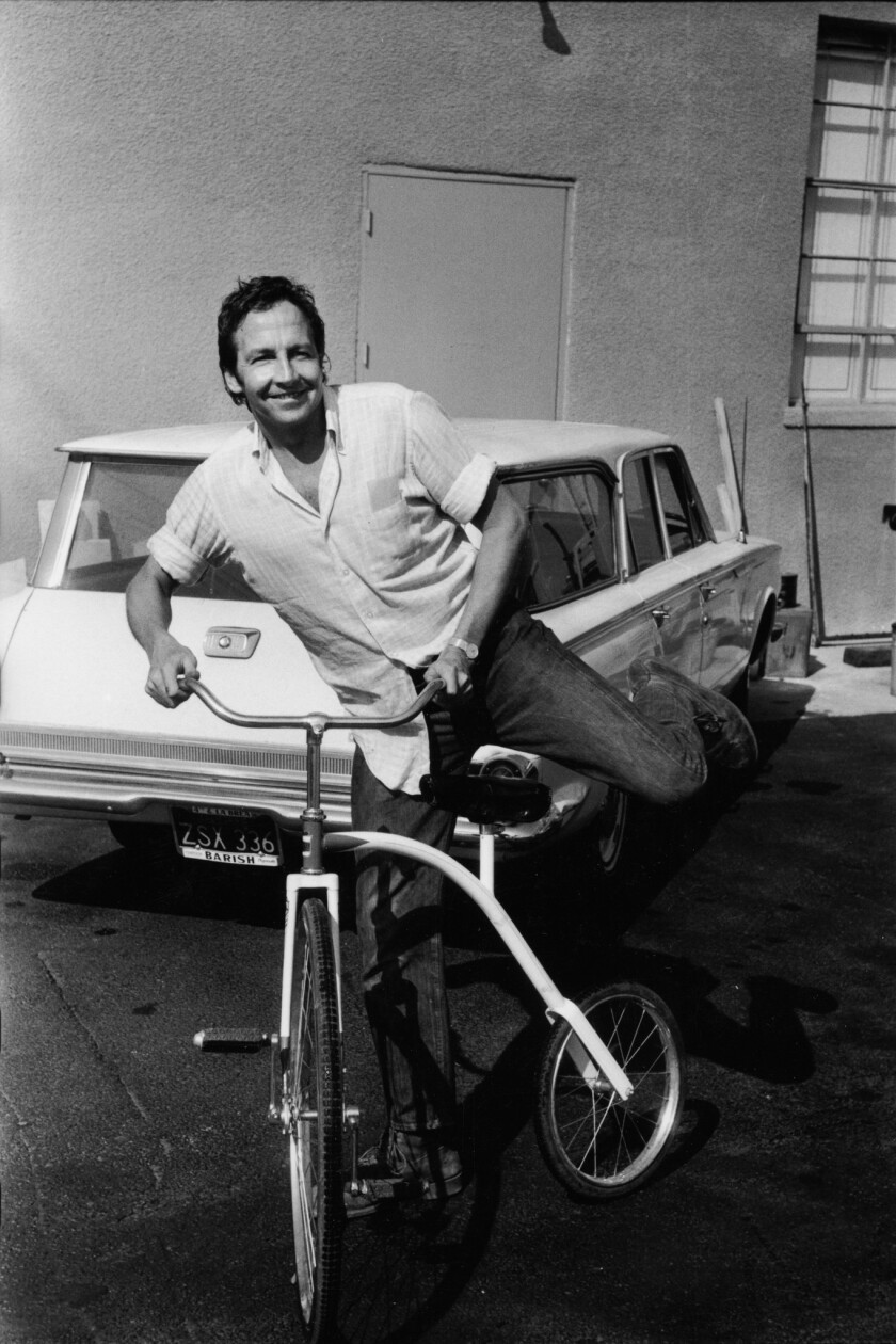 Robert Rauschenberg early in the morning cycling in the Gemini parking lot after an all night sessio