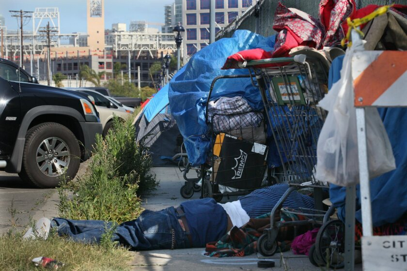 A homeless man sleeps between carts on Newton Avenue near Petco Park in Barrio Logan on Thursday. The Alpha Project had operated a tented shelter on the street until last March.