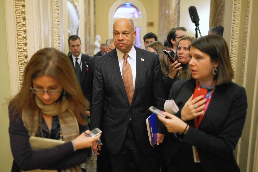 Homeland Security Secretary Jeh Johnson is surrounded by reporters as he moves between meetings with senators to discuss funding his department.