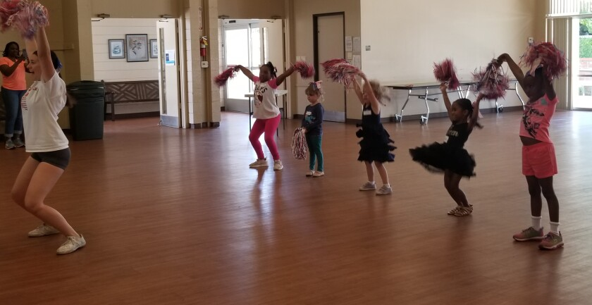 Alexandra Hill cheers with four of her students at the North Seal Beach Community Center as part of an 8-week cheerleading camp that she's leading as part of her Gold Award project.