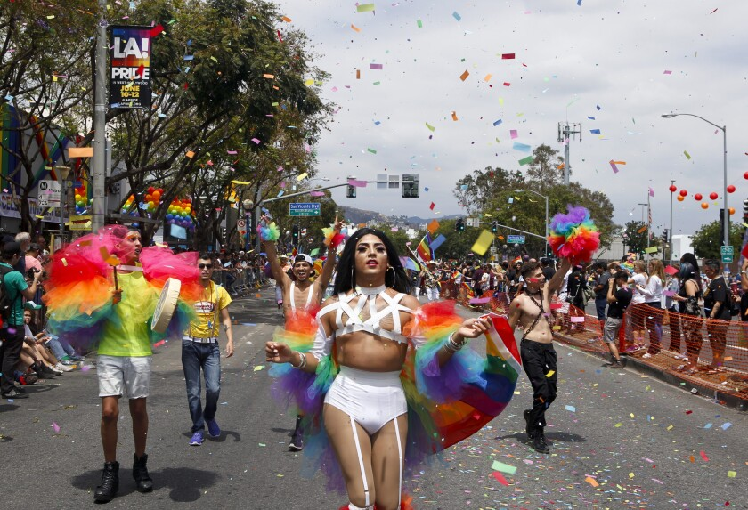 A drag queen leads a group in the LA Pride parade as rainbow confetti flies