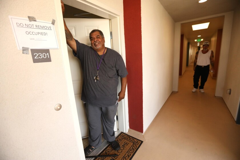 A formerly homeless man stands in the doorway of his new apartment in Bell