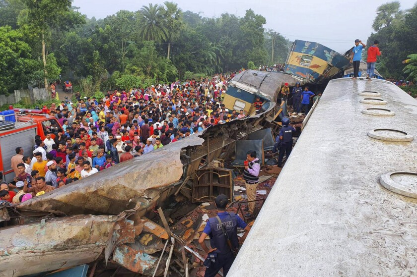 People gather near the wreckage of two trains that collided Nov. 12 in eastern Bangladesh, 51 miles east of the capital of Dhaka.