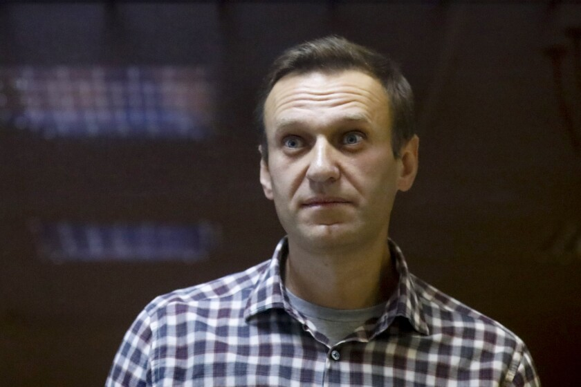 "FILE - In this Saturday, Feb. 20, 2021 file photo, Russian opposition leader Alexei Navalny stands in a cage in the Babuskinsky District Court in Moscow, Russia. Imprisoned Russian opposition leader Alexei Navalny, who has been on hunger strike since March 31, described threats to force-feed him, using ""straitjacket and other pleasures,"" in a message from behind bars Friday, April 16. In an Instagram post, Navalny said an official told him that a blood test indicated his health was deteriorating and threatened to force-feed him if he continues to refuse to eat. (AP Photo/Alexander Zemlianichenko, File)"