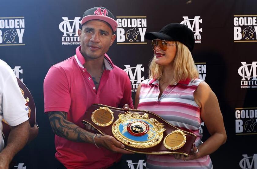 El recién retirado boxeador puertorriqueño Miguel Cotto (i) posa junto a su esposa Melissa Guzmán (d) mientras sostienen la faja de diamantes que le entregó la Organizacion Mundial de Boxeo (OMB). EFE/Archivo